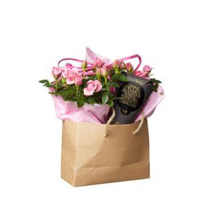 Presentpåse med rosa krukrosor och en chokladstrut. Från Interflora.