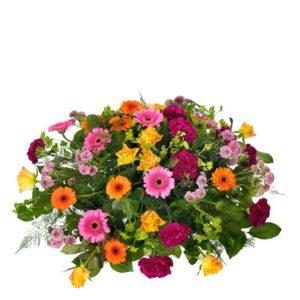 Rund begravningsdekoration med germini, rosor, nejlikor och santini. Blommorna i blandade, glada färger. En färgstark dekoration som ingår i Interfloras sortiment av begravningsblommor.