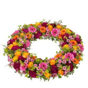 Begravningskrans med rosor, germini, santini och grönt. Blommorna i blandade, glada färger. Skicka kransen med ett blomsterbud direkt till aktuell begravning - beställ blommogrammet enkelt och snabbt på nätet.