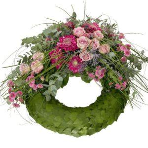 Begravningskrans med själva stommen i grönt, på toppen en dekoration med anastasia, rosor, santini och gröna strån. Blommor i lila/cerise. Begravningskransen finns att beställa online hos Interflora.