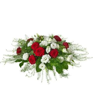Rundbunden begravningsdekoration med rosor, eustoma och tallapsi. Blommor i rött och vitt. Dekorationen ingår i Interfloras utbud av begravningsblommor.