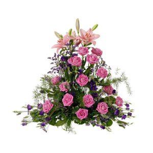 Hög begravningsdekoration med liljor, rosor, prärieklockor, limonium och dekorationsgrönt. Blommor i lila/rosa. Begravningsdekorationen finns att beställa online hos Interflora.