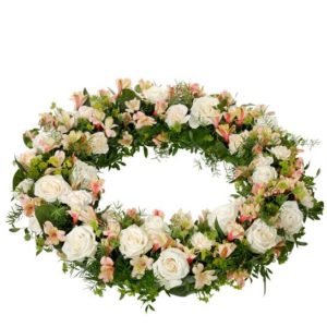 Begravningskrans med nejlikor, rosor och alstromeria. Blommor i creme och aprikos. Skicka kransen med ett blommogram från Interflora - beställ direkt på nätet.