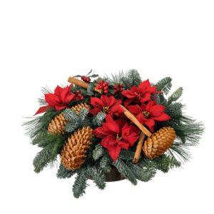 Låg julgrupp med röda julstjärnor, nobilis, kottar, kanelstänger och grönt. Skicka julgruppen med ett blommogram från Interflora och önska God Jul!