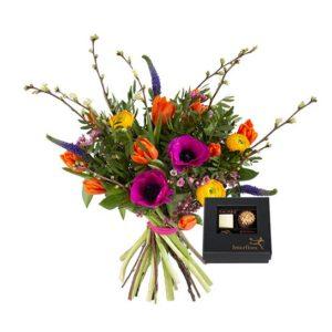 Färgstark bukett med tulpaner, anemoner, ranunkler, vaxblomma och gröna blad. Plus en ask med fyra chokladpraliner. Ett Interflora-arrangemang.