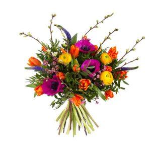 Bukett i klara, glada färger; tulpaner, anemoner, ranunkler, vaxblomma och gröna blad. Buketten ingår i Interfloras utbud av vårblommor.