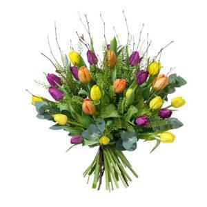 Bukett med tulpaner i gult, orange och lila tillsammans med gröna blad och blåbärsris. Skicka blommorna med ett blommogram från Interflora och önska Glad Påsk!