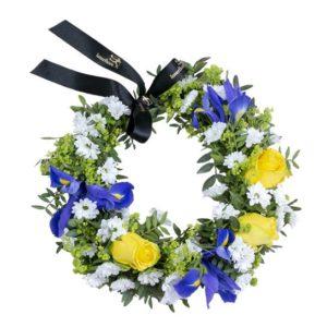 Sommarkrans med sommarblommor i gult, vitt och blått +gröna blad. Ur Interfloras utbud av sommarblommor.