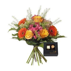 Bukett med rosor, germini, alstroemeria, kärleksört och gröna blad. Blommorna i gult, orange, rosa. En chokladask ingår. Ur Interfloras sortiment.