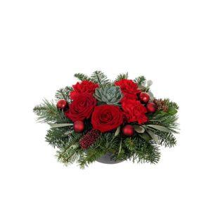Låg, liten juldekoration, med rosor, nejlikor, blandat julgrönt och röda julkulor