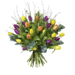 Färgglad påskbukett med tulpaner, klassisk björkris och grönt. Här i gult, lila, orange och grönt. Blommorna finns att beställa hos Interflora.