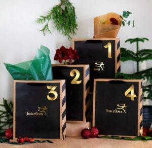 """Fyra stycken presentpåsar, var och en med ett """"hemligt"""" blommogram. Leverans med blombud fyra gånger inför adventsdagarna. Läs leveransinstruktionerna hos Interflora noggrant."""
