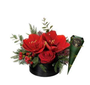 Juldekoration i rund ask, med röda snittamaryllis, ros, hypericum, grönt och så en strut med chokladpraliner som extra bonus. Beställ dekorationen hos Interflora - sänd den med ett blomsterbud!