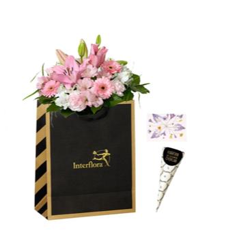 Presentpåse med blommor i rosa och vitt, plus en strut choklad. Blommografera presentsetet via Interflora!