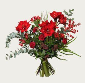 Röd amaryllis, nejlika, alstroemeria, eucalyptus och dekorationsgrönt. Beställ julbuketten som ett blommogram hos Interflora